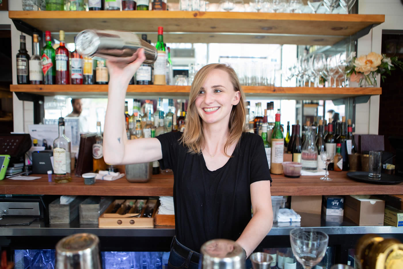 Female bartender shaking up a cocktail behind the bar with a big smile.