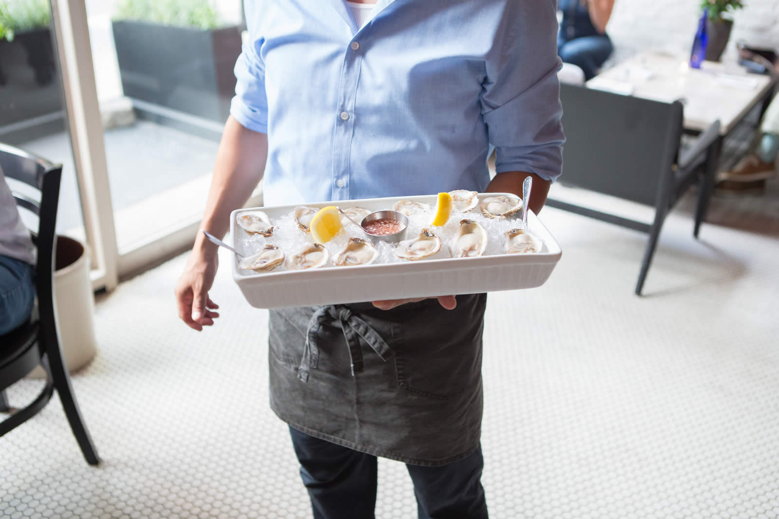 A server holding an ice-filled tray of fresh oysters.